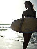 Woman standing on a sandy beach by the ocean, holding a surfboard.