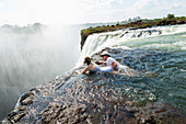 Man and a girl, father and daughter in the water of the Devil's Pool on the edge of Victoria Falls, mist rising from the falling water.