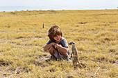 5 year old boy looking at Meerkats, Kalahari Desert, Makgadikgadi Salt Pans, Botswana
