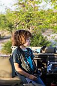 A five year old boy holding binoculars in a safari jeep.