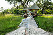 6 year old boy playing with toy airplane, tented camp, Botswana