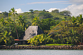 View of a beach villa with deckchairs framed by tropical vegetation, Hotel Shangri-La, Fiji