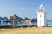 Lighthouse and boats in Barfleur harbor in the evening. The town is one of the most beautiful places in France.