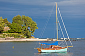 The sailing boat is anchored in a bay not far from the small port town of Saint Vaast la Hague.