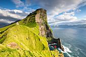Hiker above the ocean towards Kallur lighthouse, Kalsoy island, Faroe Islands, Denmark