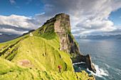 Hiker runs on steep cliffs at Kallur lighthouse, Kalsoy island, Faroe Islands, Denmark