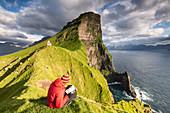 Hiker is watching the map above the ocean towards Kallur lighthouse, Kalsoy island, Faroe Islands, Denmark