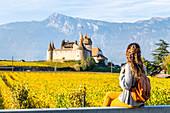 Eine junge Frau bewundert das Schloss Aigle, Aigle, Kanton Waadt, Schweiz