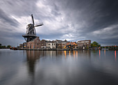 View of Windmill De Adriaan reflected in the canal of the river Spaarne during golden storm, Haarlem, Amsterdam district, Papentorenvest, Randstad, North Holland, The Netherlands, Europe