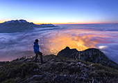 Hiker look the Lecco city wrapped of clouds from the top of Coltignone mount, Piani dei Resinelli, Lecco province, Lombardy, Italy, Europe (MR)