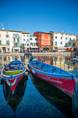 Lazise sul Garda, Verona province, Veneto, Italy, Europe. Two wooden boats in the harbour of Lazise