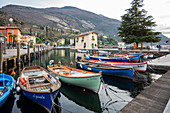 Torbole, Trento province, Trentino Alto Adige, Italy, Europe. Wooden boats moored in the harbour of Torbole