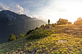 Hiker over a rock at sunset, Ozein, Aymavilles, Aosta Valley, Italy