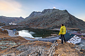 Hiker admires at sunrise the lake at Gran San Bernardo Pass, Aosta Valley, Italy, Europe