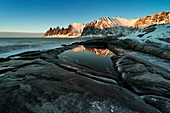 the Devil's teeth Mountain, reflections at sunset in a puddle along the Ersfjorden, Senja, Northern Norway, Europe.