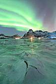 the Northern Lights draw their magic in the sky, illuminating Flakstapollen, municipality of Flakstad, Flakstadoya, Nordland, Lofoten islands, Norway, Scandinavia, Europe