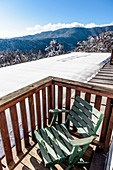 Chair on balcony in front of snowy landscape, Himmelberg, Carinthia, Austria