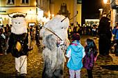 A Krampus talks to the children in the old town, Klausenttrieb, Immenstadt im Allgäu, Oberallgäu, Bavaria, Germany, Europe