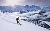 Snowboarder auf Splitboard im Tiefschnee bei der Abfahrt im Karwendel am Schafreiter, Tirol, Österreich