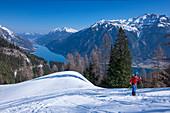 Man on ski tour on Achensee to the summit of Bärenkopf in spring