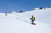 Snowboarder Turn mit Splitboard im Tiefschnee in den Zillertaler Alpen, Hochfügen, Winter in Tirol, Österreich