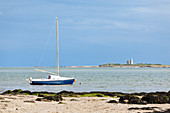 Sailboat moored at Saint Vaast la Hougue, Cotentin Peninsula, Normandy, France. In the background the island of Tatihou with the Vauban tower.