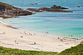 Summer on the beach below Cap Erquy in Brittany with bathing vacationers.