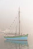Altes Segelschiff im Hafen von Equy im dichten Morgennebel. Bretagne, Cote d Armor, Frankreich