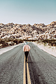 Woman running on road in Joshua Tree National Park, Los Angeles, California, USA, North America