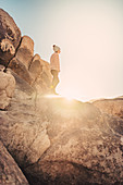 Woman hikes between rocks in Joshua Tree National Park, Los Angeles, California, USA, North America