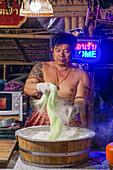 Thai in traditioneller Kleidung formt Nudeln auf dem Nachtmarkt Kungsri in Ayutthaya, Thailand