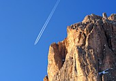 Condensation streams from an airplane, rocks, mountain, Val Gardena in winter, Dolomites, South Tyrol, Italy