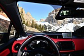 From the car on the pass road of the Sella Joch, driver, steering wheel, rocks, windshield, view, scenery, Dolomites, Trentino in winter, Italy