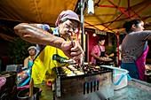 Krabi Town, Thailand - November 23 2019: An elderly Thai woman prepared fried eggs off bird  in Krabi Weekend Night Market in Krabi Town, Thailand.