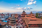 Kathmandu, Nepal - March 9 2020: Aerial view of Patan Durbar Square. People strolling around the temple premises. Pinncale of Temples and himalaya in the backdrop.