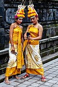Two Young Balinese Hindu Females Looking At A Mobile Phone (Cell Phone) At The Batara Turun Kabeh Ceremony, Besakih Temple, Bali, Indonesia.