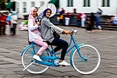 Young Indonesian Women Cycling In Taman Fatahillah Square, Jakarta, Indonesia.