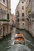 cityscape with motorboat in narrow canal with historical buildings, shot in bright cloudy fall light at Venice, Veneto, Italy\n