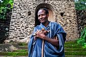 Debre-Sina-Beta-Maryam-Kirche, Lake Tana, Bahir Dar, Äthiopien. Ein Priester posiert majestätisch mit seinem Kreuz an der Tür des Birgida-Maryam-Klosters auf einer der Inseln des Tana-Sees. Der Tana-See, der größte See Äthiopiens, ist die Quelle des Blauen Nils, von wo aus er seine lange Reise nach Khartum und weiter ins Mittelmeer beginnt.