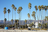 Homeless people on the beach against the backdrop of the Santa Ynez Mountains in Santa Barbara, California, USA.