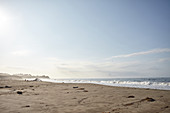 Silhouettes of young children on the beach at Hearst San Simeon State Park in the early morning, California, USA.