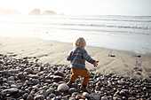 Little child plays on the autumnal beach in Big Sur, California, USA.