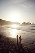 Last visitors enjoy the sunset on Big Sur Beach, California, USA.