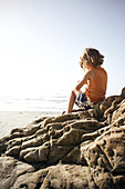 Child sitting on a rock on Big Sur Beach, California, USA.