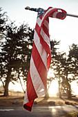 Verwickelte Amerikanische Flagge im Abendlicht auf einem Parkplatz bei Big Sur am Highway 1, Kalifornien, USA.