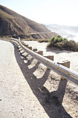 Guardrail on Highway 1 with a view of the Santa Lucia Range and the Pacific Ocean, Big Sur State Park, California, USA.