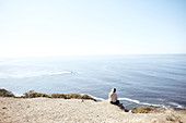 Young woman sits on a cliff and looks out over the Pacific Ocean on the edge of Highway 1, Big Sur State Park, California, USA.