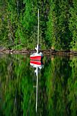 Ein Segelboot im See spiegelt sich im Wasser, Junsele, Norrbottens Län, Schweden