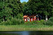 Small, red Swedish house by a lake, Vidöstern, Toftaholm, Jönköpings Län, Sweden