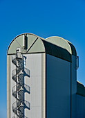 Grain elevator with spiral staircase against a deep blue sky in Skara, Sweden